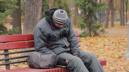 shameful : Male drinking addict sleeping on bench in autumn park, alcohol abuse problem