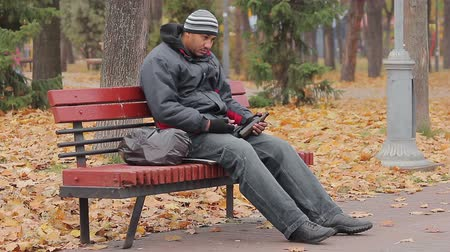 shameful : Drunk man sleeping on bench in park with bottle in hand, alcohol use disorder