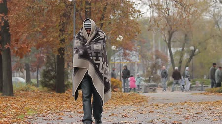 deprived : Miserable poor man walking in city park covered from cold with shabby blanket