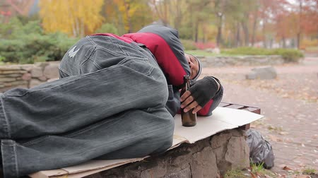 shameful : Drunk alcoholic sleeping on bench with empty bottle in hand, insolvent person