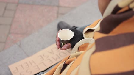 deprived : Poor person begging for charity in city street, sympathetic people giving money Stock Footage