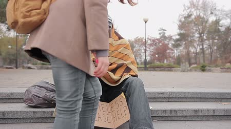 dobrosrdečný : Kind young woman giving money to poor homeless man begging for help in street