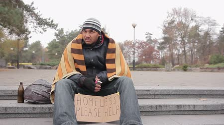 deprived : Homeless man in shabby clothes sitting in city park with sign asking for help Stock Footage