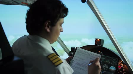aircrew : Serious aircrew commander filling in flight papers, autopilot steering plane Stock Footage
