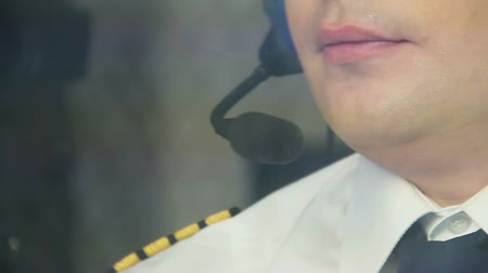 perspiring : Exhausted captain operating airliner and talking to co-pilot on headset