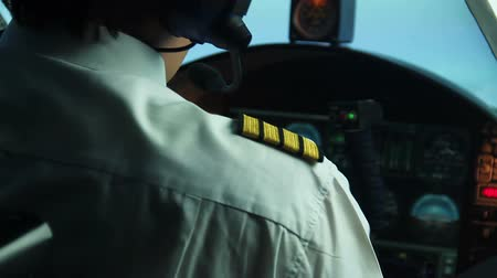 pilot in command : Male pilot checking control panel and reporting situation to flight dispatcher
