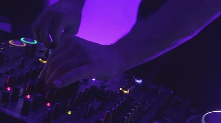 tweaking : Closeup shot of male dj hands turning controls on sound equipment at club party Stock Footage