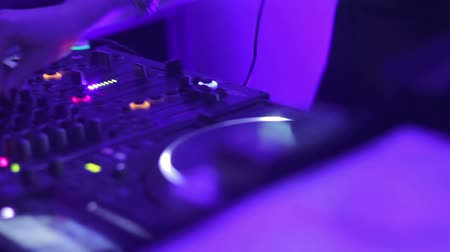 tweaking : Hands of female dj turning controls on professional sound equipment in nightclub