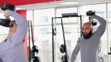 self motivated : Male athlete exercising with heavy dumbbell in gym, looking at mirror reflection Stock Footage