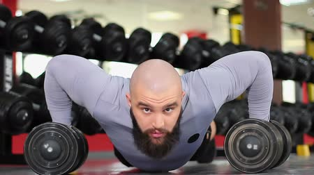 feszült : Bearded male athlete doing dumbbell push-ups, bodybuilder training intensively