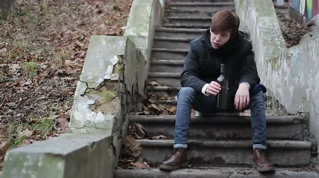 taciz : Drunk guy sitting on abandoned stairs in park with bottle in hand, alcoholism Stok Video