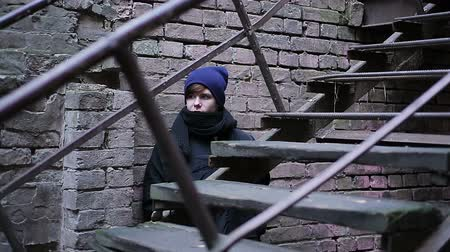 bullies : Scared male teenager hiding behind old brick building, looking out cautiously Stock Footage