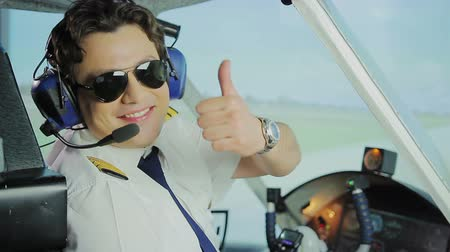 aircrew : Happy male pilot in sunglasses smiling at camera, making thumbs up hand sign Stock Footage