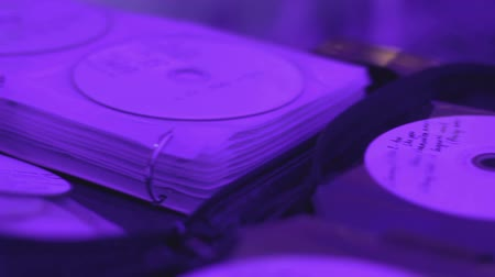 tweaking : Pile of cd records lying on table, dj performing for audience, party atmosphere