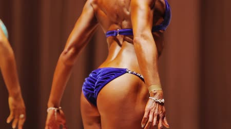 bicep : Tanned lady showing back double biceps pose at bodybuilding competition, fitness