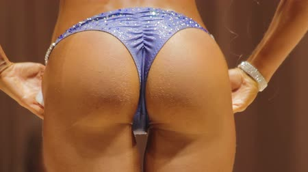 calcinhas : Seductive lady in sparkling bikini demonstrating sexy butt at beauty contest