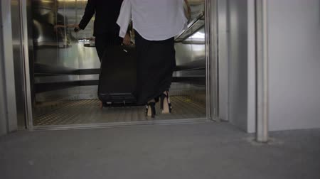 лифт : Young man and woman with luggage entering elevator at airport or railway station