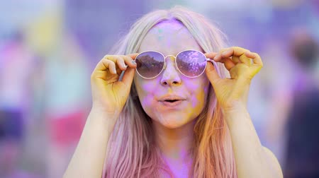 dyes : Girl in sunglasses covered in colorful dyes smiling, blowing air kiss to camera