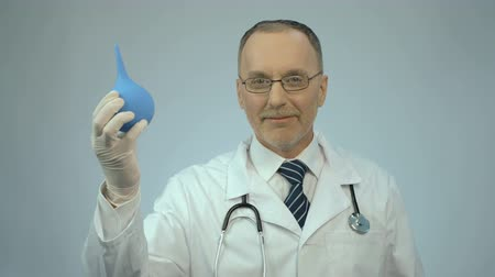 rubber enema : Happy smiled proctology doctor showing rubber syringe and looking at camera