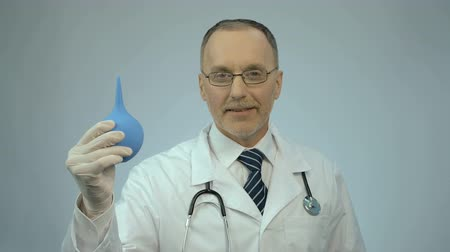 rubber enema : Funny doctor pressing on rectal syringe with smile on face, proctologist joking Stock Footage