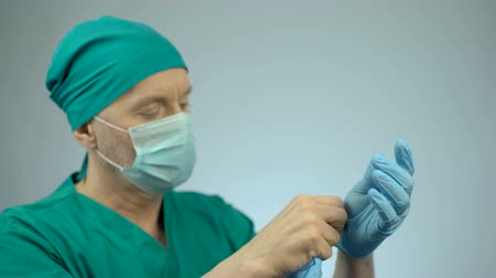 tényező : Disappointed surgeon taking off medical gloves after unsuccessful operation