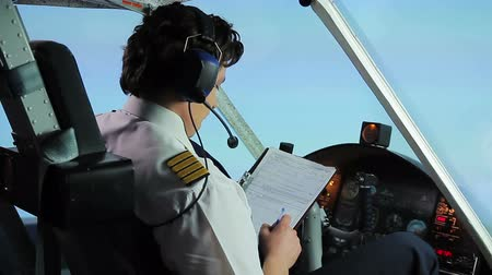 aircrew : Professional pilot filling out flight papers while flying airplane, profession