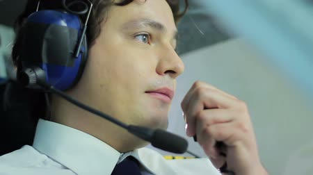pilot in command : Handsome pilot talking to traffic controller while flying airliner, job duties