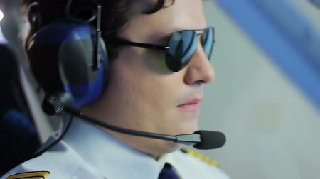 prestigious : Young pilot wearing sunglasses and steering airliner, prestigious profession
