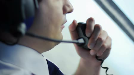 pilot in command : Airman talking to co-pilot by walkie-talkie and discussing flight details Stock Footage