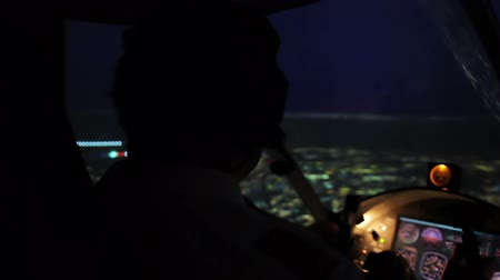 nightcity : Pilot in headset maneuvering airplane above evening city, responsible job Stock Footage