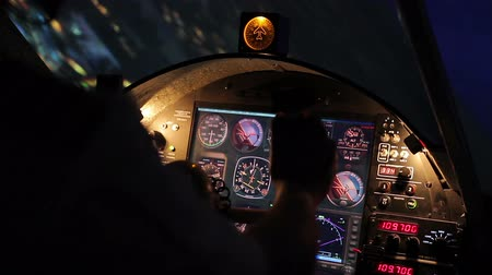 nightcity : Aircrew commander flying plane above night city, flight panel with indicators Stock Footage