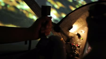 nightcity : Close-up of pilot hands on steering wheel, night flight above illuminated city
