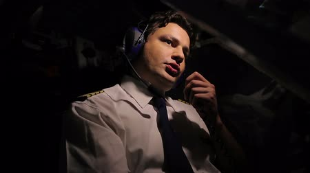 pilot in command : Concentrated aircrew commander steering plane and talking by walkie-talkie