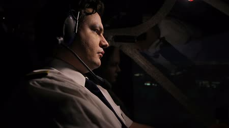 chartered : Night voyage over the city, attentive pilot steering airliner professionally Stock Footage