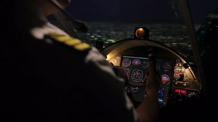 aircrew : Attentive pilot steering aircraft professionally, night flight above megalopolis