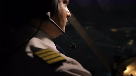chartered : Attentive captain pilot in headset navigating huge airliner at night, job duties Stock Footage