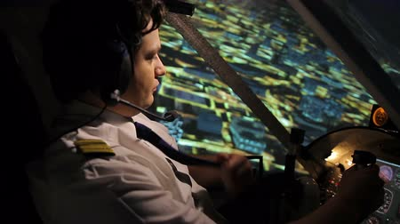 chartered : Commercial pilot in beautiful uniform controlling airplane above night city Stock Footage