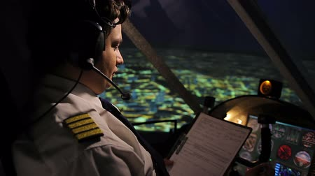aircrew : Pilot reading and filling out flight form, navigating plane in autopilot mode