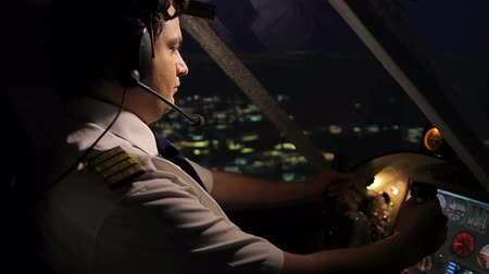 aircrew : Professional aircrew commander navigating airplane above city at night time