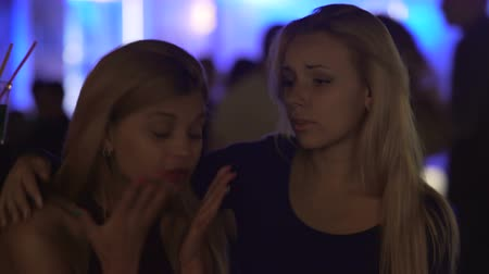 Łzy : Compassionate young woman supporting upset female friend at nightclub party
