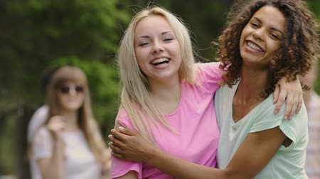 гей : Young beautiful female couple hugging, looking into camera, smiling at party