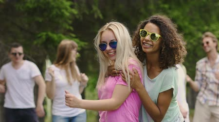гей : Two multiracial females happily dancing outdoors, young people enjoying party