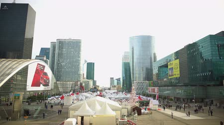 arche : Large tents in city center, street fair, people walk near modern glass buildings