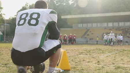 замена : Football player watching game from sideline, teams taking positions, slow-mo