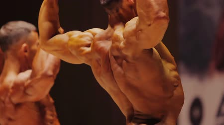 feszült : Professional male bodybuilders showing huge muscles in back double biceps pose
