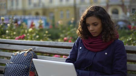 notebooklar : Young biracial writer working on new project, sitting with laptop outdoors