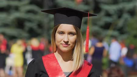 čepice : Beautiful young woman in academic dress looking to camera, successful graduate