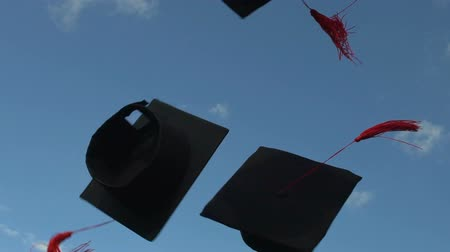 čepice : Academic mortarboards thrown up in clear blue sky by carefree happy graduates