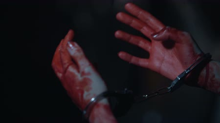 kajdanki : Close-up of bloody trembling murderers hands in handcuffs, crime and punishment