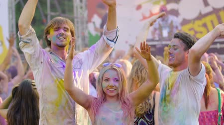 gençlik kültürü : Young smiling people covered in colorful powder dancing at Holi festival concert Stok Video